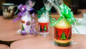 圣诞节蜡烛包装了与在桌上的五颜六色的丝带 免版税图库摄影