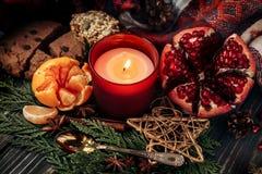 圣诞节蜡烛和礼物用红色丝带和石榴石曲奇饼 库存图片