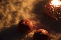 圣诞节蜡烛和蜜桔在雪在黑暗 图库摄影