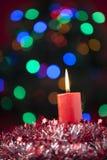 圣诞节蜡烛有五颜六色的光背景 免版税库存照片