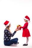 圣诞节衣裳的年轻女儿给她的母亲圣诞节礼物 图库摄影