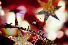 圣诞节装饰、充满活力的金黄星、银色链子和bokeh 免版税库存照片