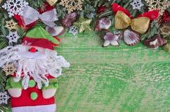 圣诞节装饰、圣诞老人和巧克力 与杜松分支的老绿色木背景,一个地方为 库存照片