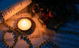 圣诞节装饰、灼烧的蜡烛和活页乐谱 免版税库存照片