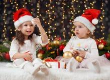 圣诞节装饰与礼物,黑暗的背景与照明和boke的两个女孩点燃,寒假概念 免版税图库摄影
