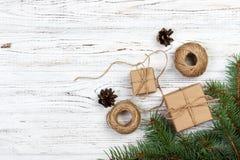 圣诞节装饰元素:串, chrtistmas树枝与锥体和数装饰了礼物在白色木背景 免版税库存照片