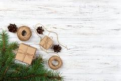 圣诞节装饰元素:串, chrtistmas树枝与锥体和数装饰了礼物在白色木背景 库存图片