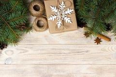 圣诞节装饰元素:串, chrtistmas树枝与锥体和数装饰了礼物在白色木背景 免版税图库摄影