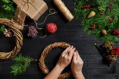 圣诞节装饰制造商用他们自己的手 圣诞节花圈为假日 庆祝新年度 顶层 图库摄影