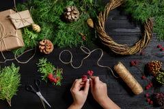 圣诞节装饰制造商用他们自己的手 圣诞节花圈为假日 庆祝新年度 顶层 免版税图库摄影