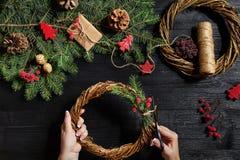 圣诞节装饰制造商用他们自己的手 圣诞节花圈为假日 庆祝新年度 顶层 免版税库存照片