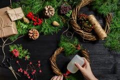 圣诞节装饰制造商用他们自己的手 圣诞节花圈为假日 庆祝新年度 顶层 库存照片