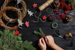 圣诞节装饰制造商用他们自己的手 圣诞节花圈为假日 庆祝新年度 顶层 免版税库存图片