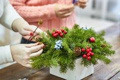 圣诞节装饰制造商用他们自己的手 有枝杈的圣诞节礼物为假日 庆祝新年度 免版税库存图片