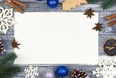 圣诞节装饰卡片问候,白色雪花橙色棒棒糖灰色木背景,蓝色圣诞节球 库存图片