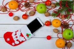 圣诞节装饰和一只袜子与一个智能手机在木ba 图库摄影
