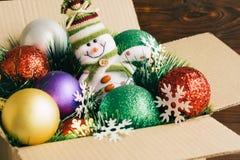 圣诞节装饰和玩具在一个纸板箱在木ba 库存照片