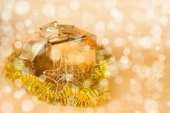 圣诞节装饰和礼物盒在一金黄bokeh 图库摄影