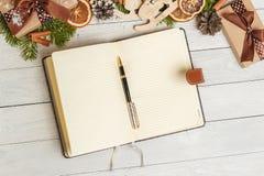 圣诞节装饰品和一个开放空白的笔记本在一张轻的木桌上 库存照片