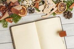 圣诞节装饰品和一个开放空白的笔记本在一张轻的木桌上 免版税库存图片