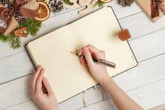 圣诞节装饰品和一个开放空白的笔记本在一张轻的木桌上 库存图片