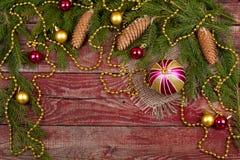 圣诞节装饰品和冷杉球果在木背景 免版税库存图片