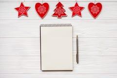 圣诞节装饰品和笔记本和笔在白色木背景 看板卡例证向量xmas 新年好 平的位置 复制空间 库存照片
