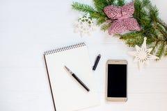 圣诞节装饰品和笔记本和笔在白色木背景 看板卡例证向量xmas 新年好 平的位置 复制空间 免版税图库摄影