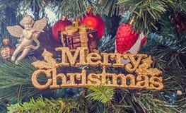圣诞节装饰品,响铃,垂悬的地球,闪闪发光,雪剥落,金子,圣诞快乐,绿色树 库存照片