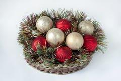 圣诞节装饰在一个柳条筐在 背景查出的白色 免版税库存照片