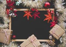 圣诞节装饰在与红色装饰和一个空的标志的木问候、圣诞快乐和愉快的N的背景或者卡片 免版税库存照片
