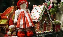 圣诞节装饰在玩具商店窗口里包括传统红色ragdoll和华而不实的屋 免版税库存照片