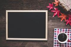 圣诞节装饰在老木背景用热的咖啡、红色装饰和一张空的标志或者卡片问候的, 库存照片