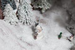 圣诞节装饰大装饰玩具 人们在森林附近做在露天场所的一个雪人 免版税库存照片