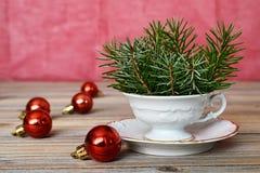 圣诞节装饰想法:圣诞节球和云杉的分支在瓷杯子安排了 库存图片