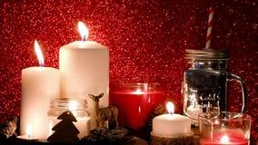 圣诞节装饰新年度 被弄脏的bokeh假日背景 红色蜡烛闪烁在旁边 金属螺盖玻璃瓶,棒棒糖 股票录像