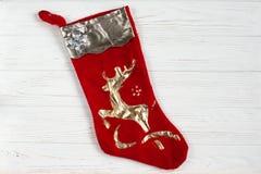 圣诞节装饰新的储存岁月 与金黄鹿的红色袜子在白色土气w 免版税图库摄影