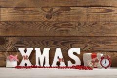 圣诞节装饰生态学木 抽象空白背景圣诞节黑暗的装饰设计模式红色的星形 手表、蜡烛和Xmas在木桌上发短信 免版税库存照片