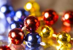 圣诞节装饰生态学木 锋利的红色和锋利和蓝色小珠,发光的黄色小珠串  免版税库存照片