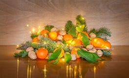 圣诞节装饰用新鲜的普通话、核桃和彩色小灯 免版税图库摄影
