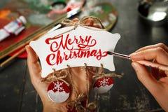 绘圣诞节装饰的手 免版税图库摄影