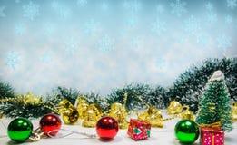 圣诞节装饰背景在蓝色,绿色,红色和金铃的丝毫雪花 免版税图库摄影