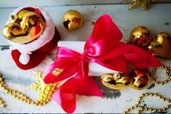 圣诞节装饰被隔绝的白色 有三金黄球的红色和金黄礼物盒和花饰 顶视图 方形的混合涂料 免版税库存照片