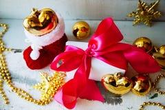 圣诞节装饰被隔绝的白色 有三金黄球的红色和金黄礼物盒和花饰 顶视图 方形的混合涂料 库存图片