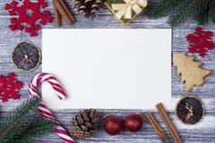 圣诞节装饰贺卡红色雪花橙色糖果,藤茎灰色木背景 免版税库存照片