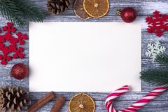 圣诞节装饰贺卡红色雪花橙色糖果,藤茎灰色木背景 免版税图库摄影