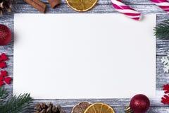 圣诞节装饰贺卡红色雪花橙色糖果,藤茎灰色木背景 库存照片