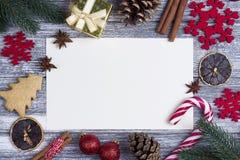 圣诞节装饰贺卡红色雪花橙色糖果,藤茎灰色木背景 图库摄影