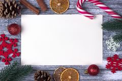 圣诞节装饰贺卡红色雪花橙色糖果,藤茎灰色木背景 免版税库存图片