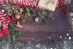 圣诞节装饰顶视图-充分红色碗冷杉锥体,在牛皮纸包裹的礼物盒,金黄天使,杉木分支, candl 免版税库存照片